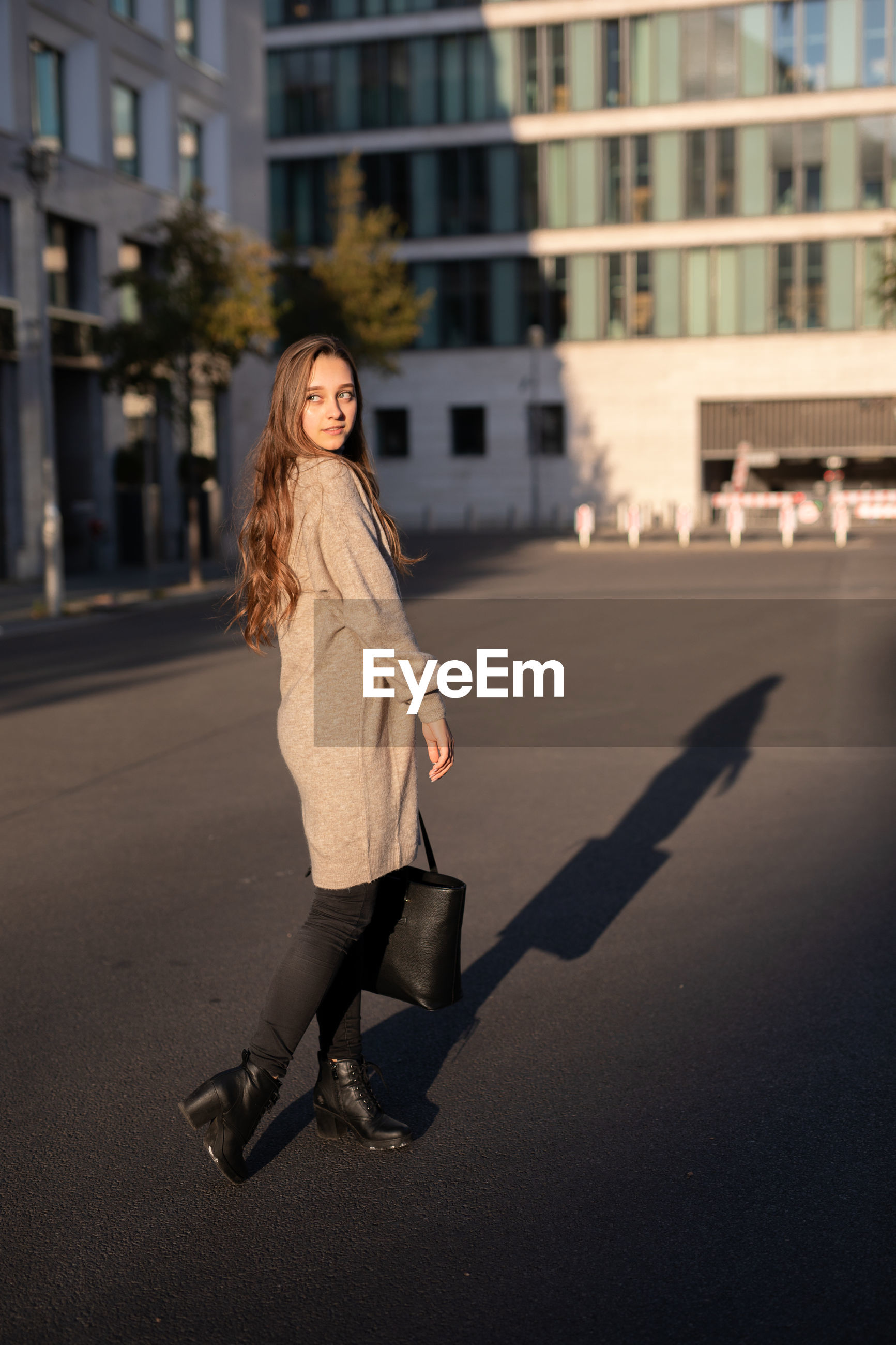 Young woman looking away while standing on city street