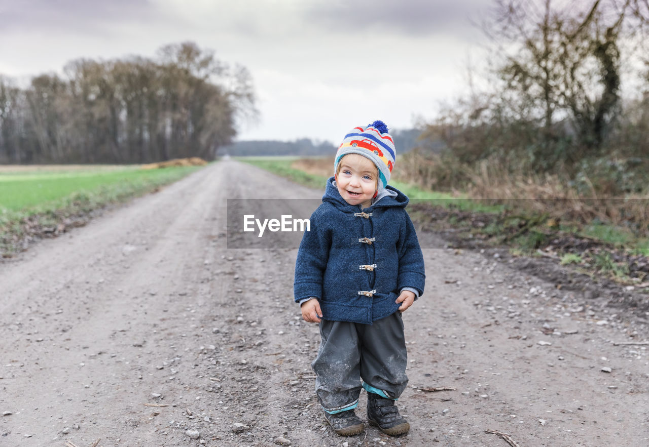 childhood, child, front view, full length, one person, clothing, road, looking at camera, winter, warm clothing, real people, men, casual clothing, portrait, standing, day, innocence, leisure activity, outdoors