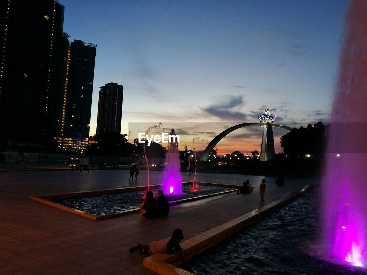 architecture, water, city, built structure, building exterior, skyscraper, sky, leisure activity, illuminated, sunset, modern, cityscape, swimming pool, real people, men, outdoors, day, people
