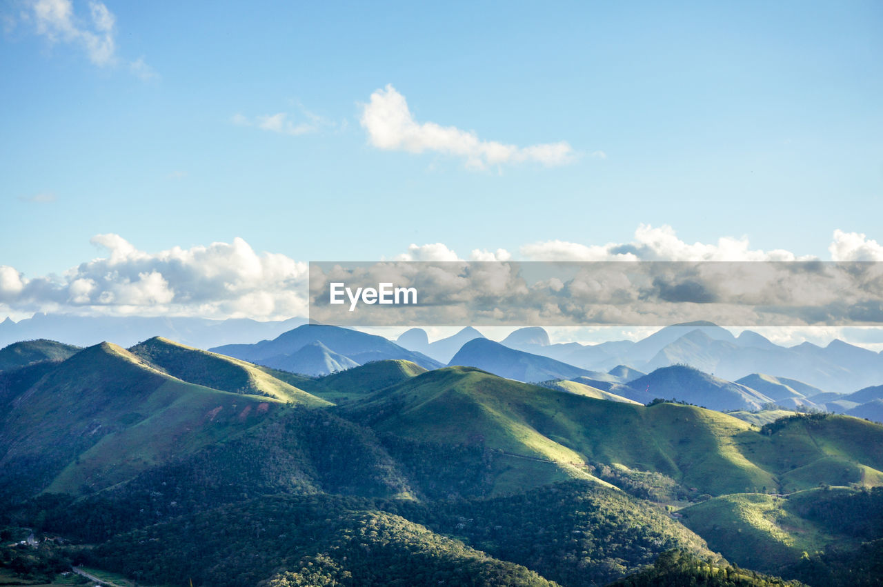 Aerial view of green mountains against blue sky