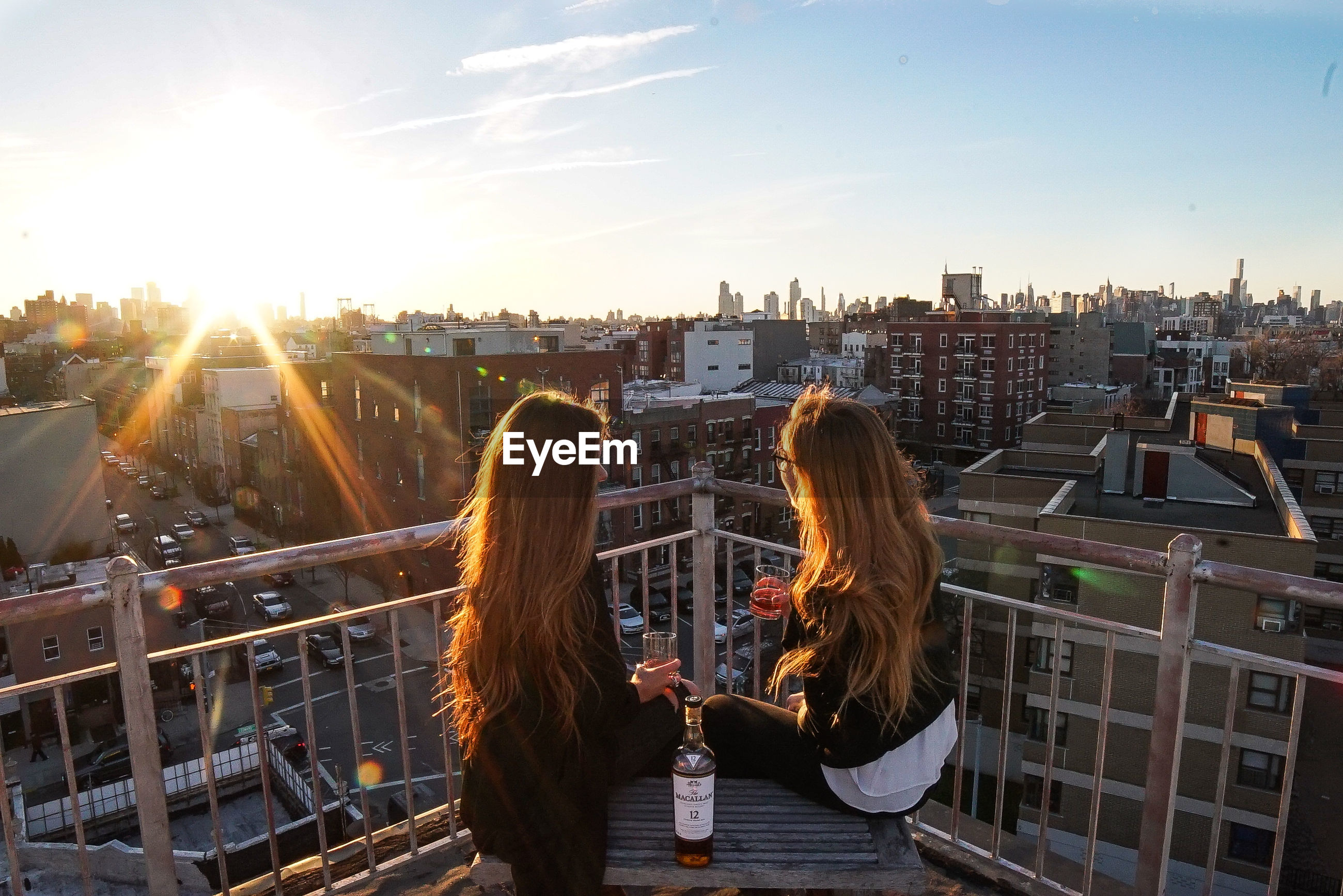 built structure, building exterior, architecture, two people, city, cityscape, sunset, sunlight, women, young women, real people, sun, young adult, togetherness, city life, skyscraper, outdoors, sky, lifestyles, urban skyline, men, friendship, day, adult, people