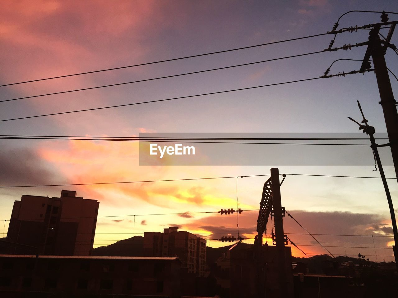 sunset, silhouette, sky, cable, architecture, cloud - sky, connection, built structure, low angle view, building exterior, outdoors, real people, technology, nature, electricity pylon, city, day