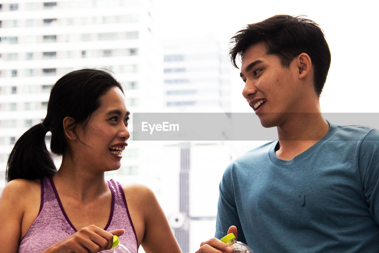 Smiling young couple looking at each other while holding water bottle