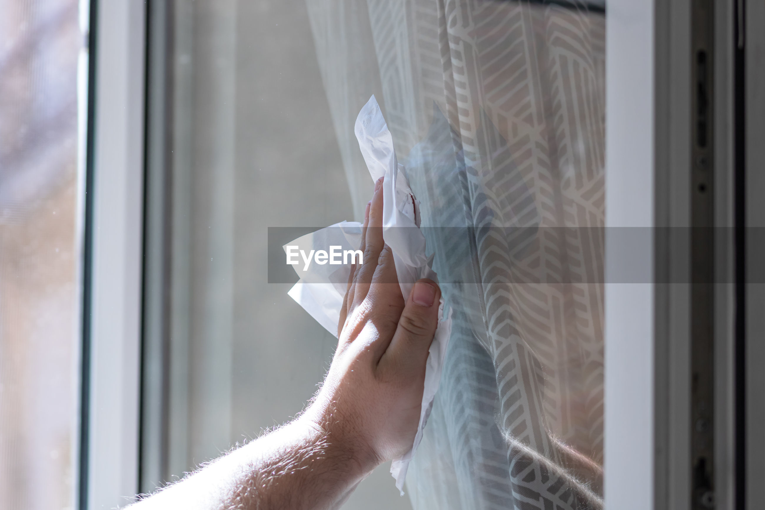 Midsection of person holding paper against window