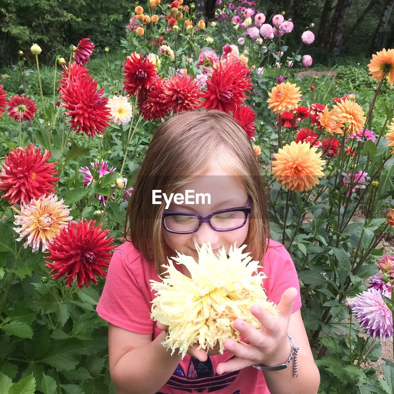 Cute smiling girl smelling yellow dahlia in park