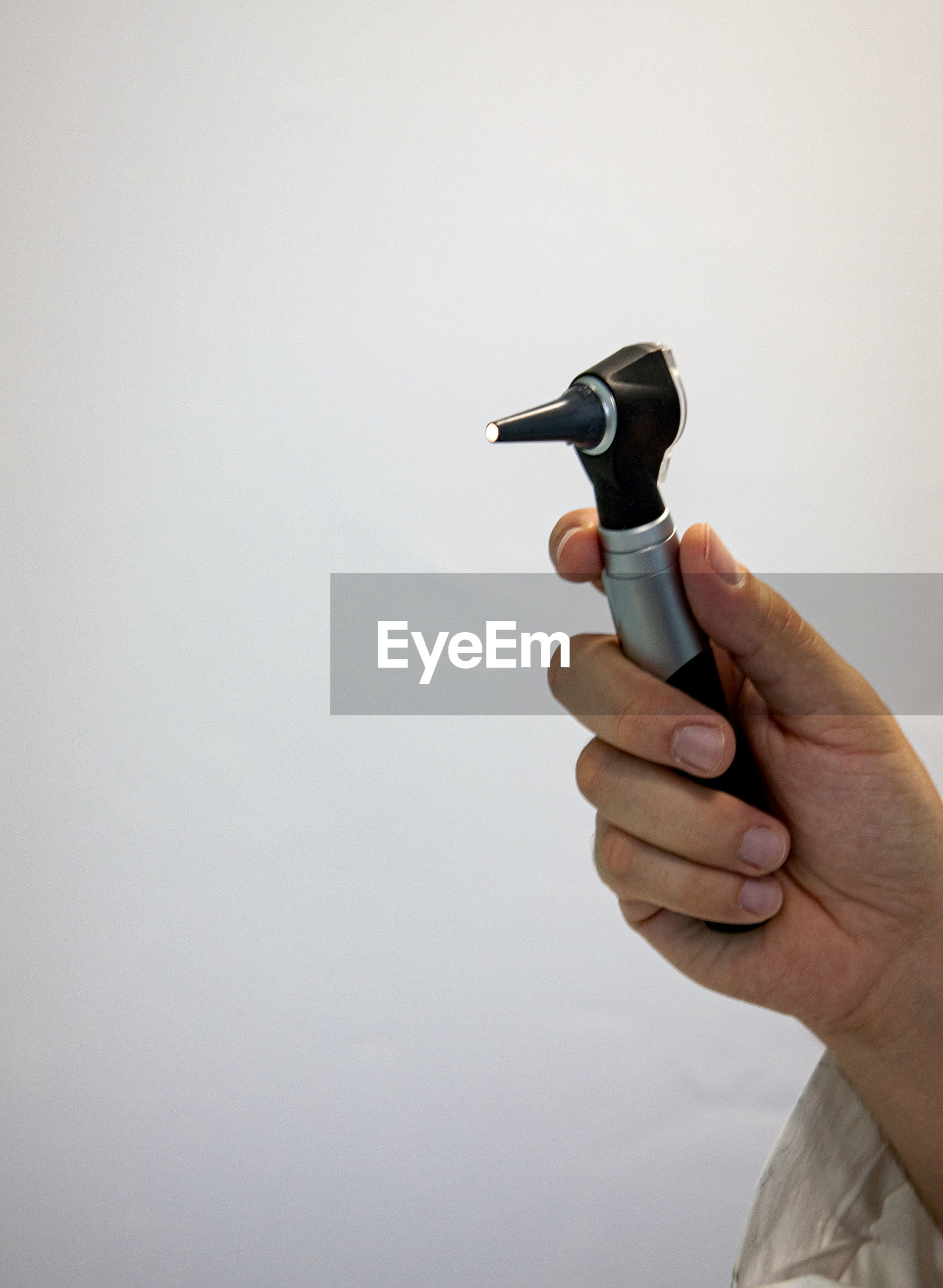 Cropped hand of person holding otoscope against white background