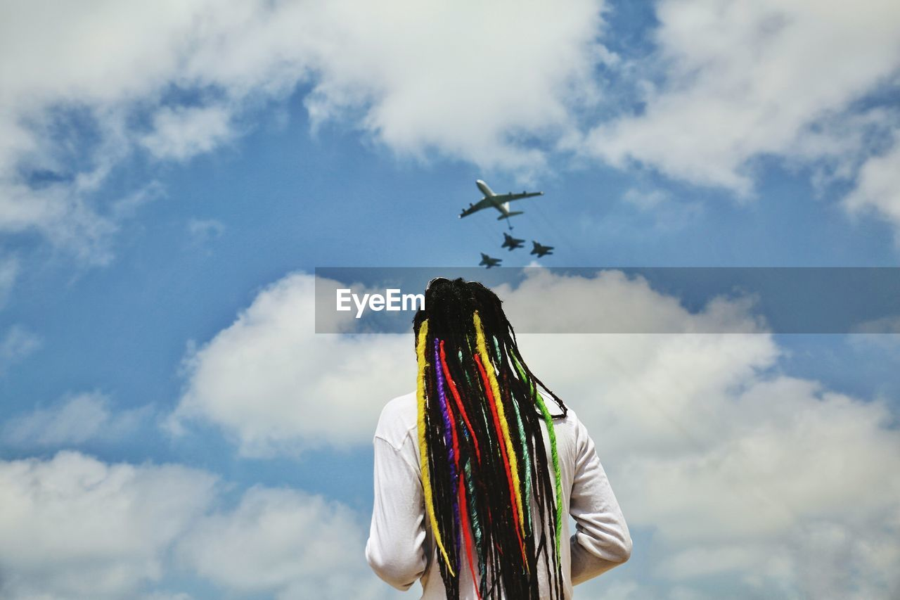 Rear view of man with colorful dreadlocks looking at airplanes flying against cloudy sky