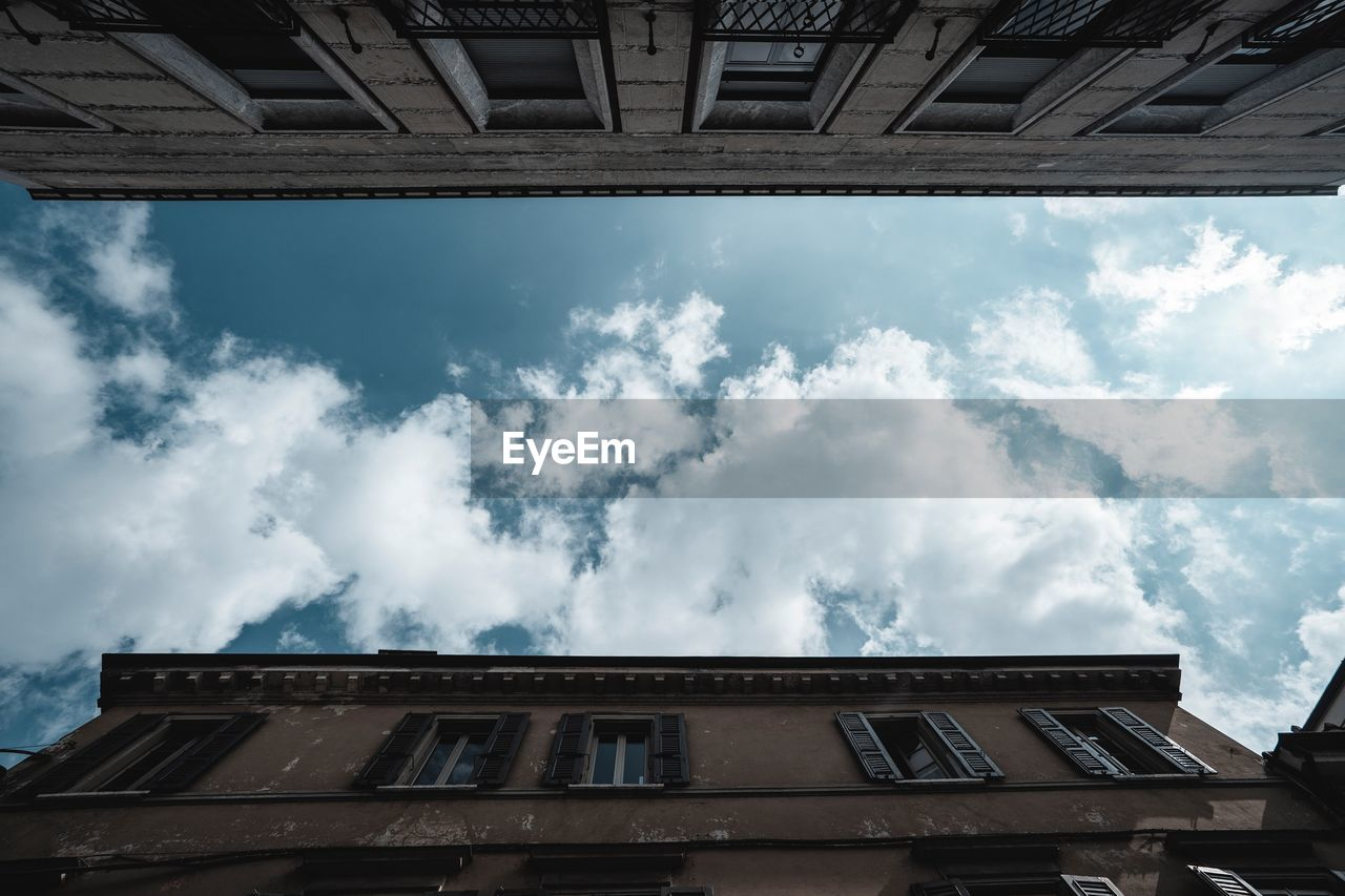cloud - sky, built structure, architecture, building exterior, sky, low angle view, building, window, nature, no people, day, residential district, outdoors, city, roof, glass - material, apartment, sunlight, house, ominous