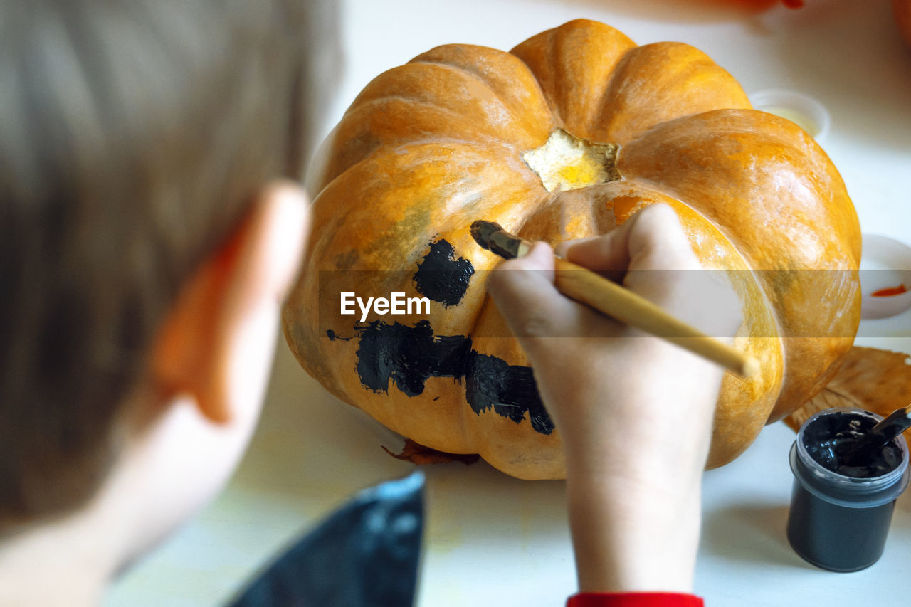 Rear view of boy painting pumpkin at home