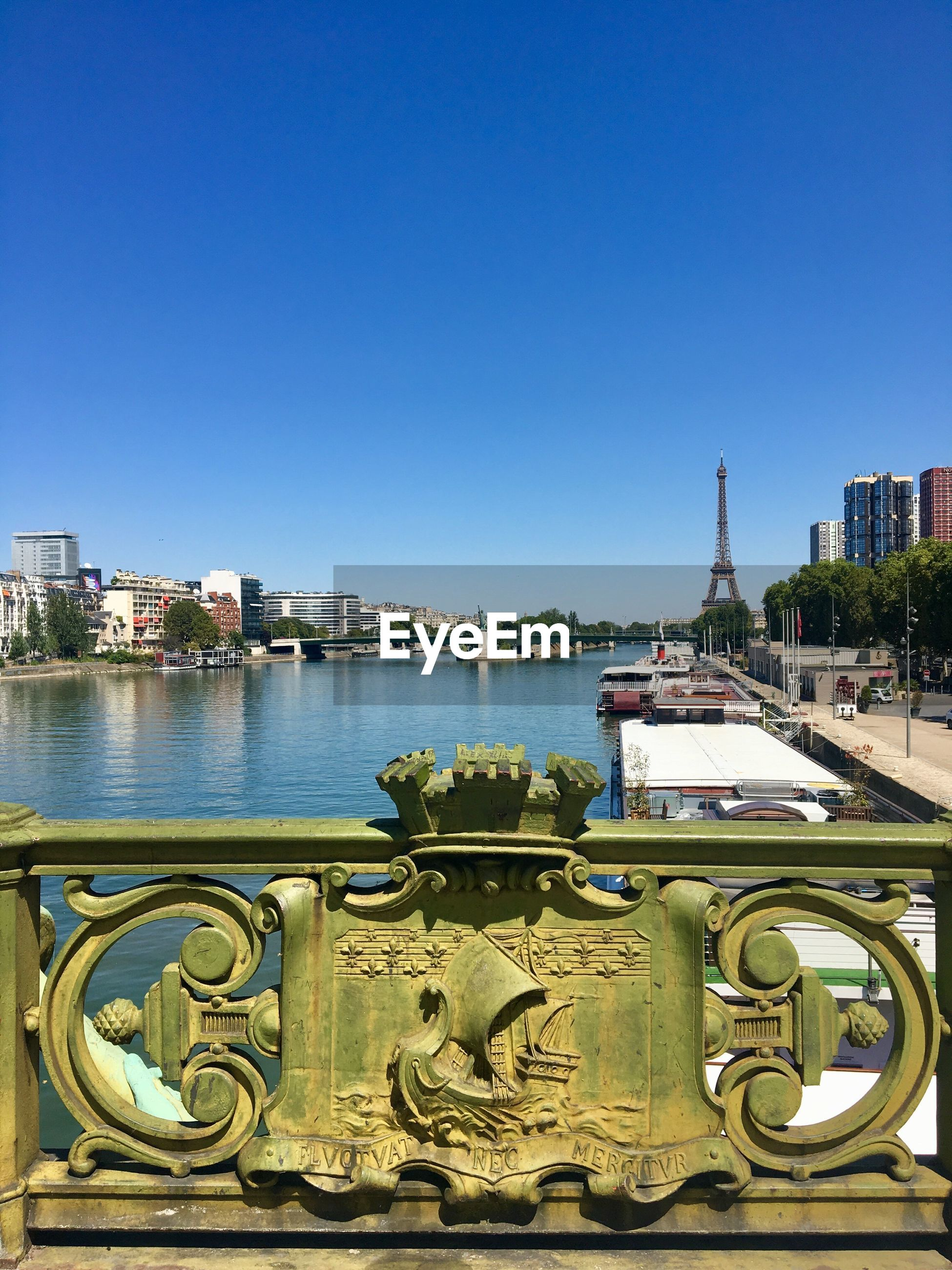 View of river and eiffel tower against clear blue sky