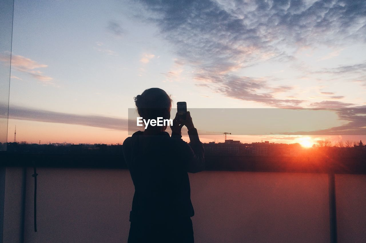 Rear View Of Woman Photographing By River Against Sky During Sunset