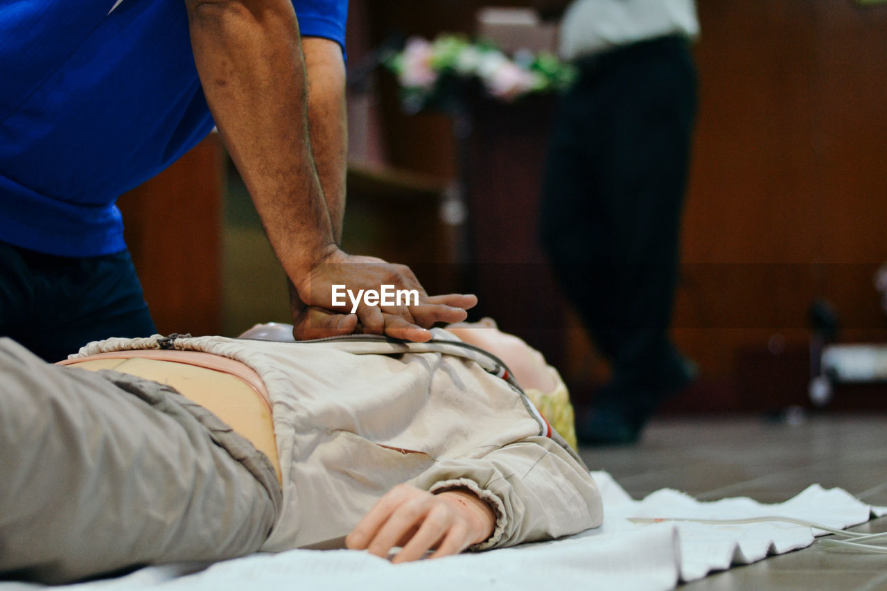 Midsection of man performing cpr on dummy