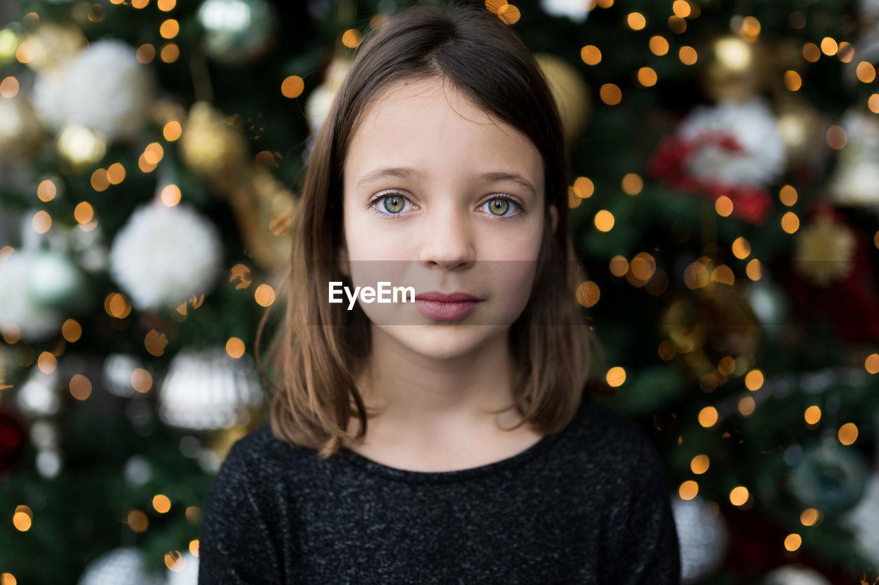 Portrait of girl against christmas tree