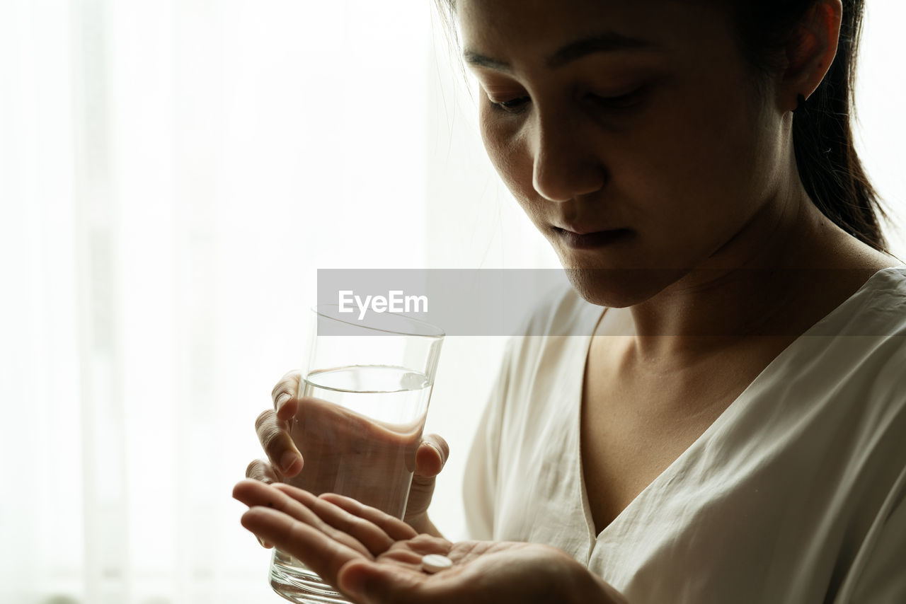 Close-up of woman having medicine