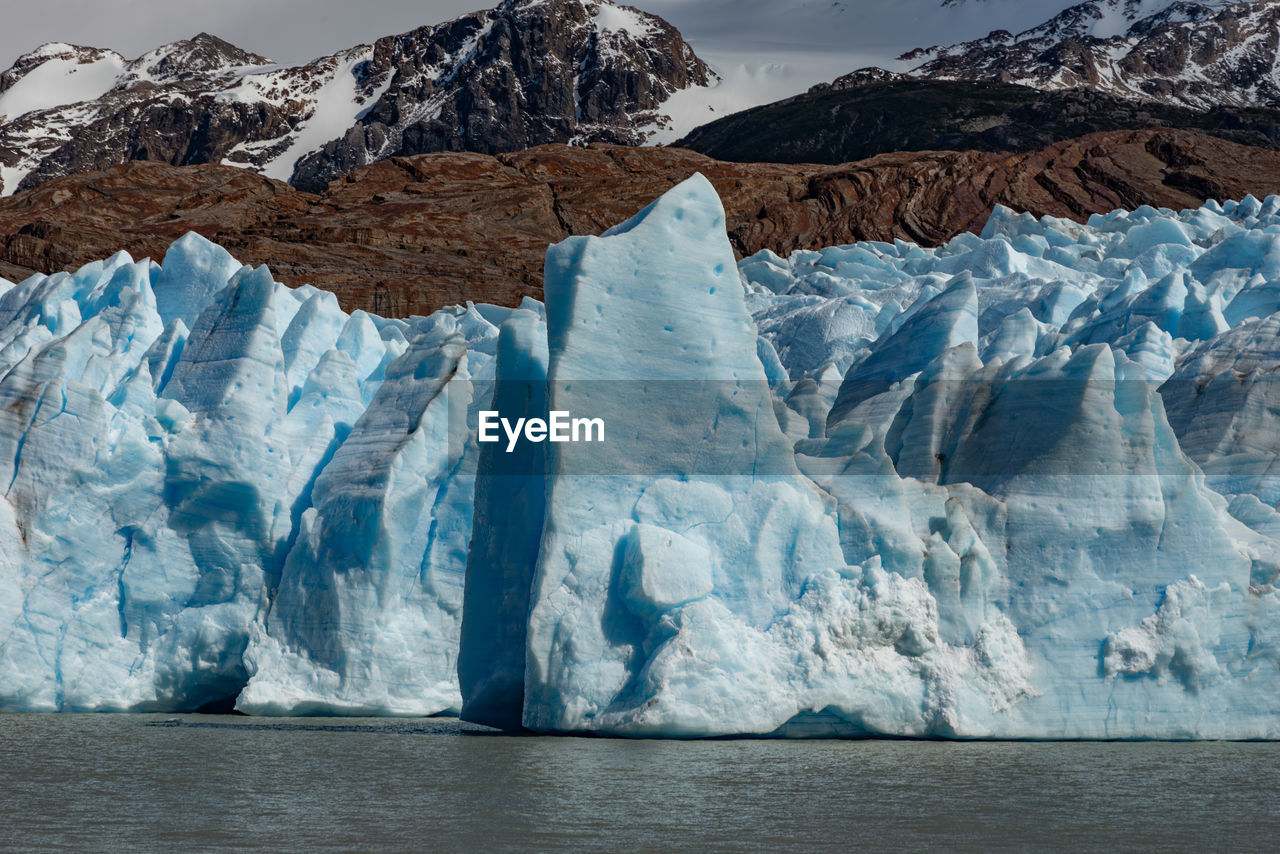 Scenic view of frozen sea against mountain