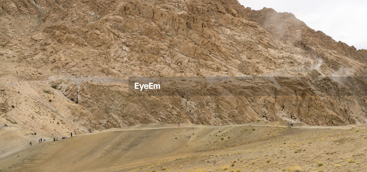 mountain, beauty in nature, nature, rock, tranquility, day, mountain range, scenics - nature, rock formation, transportation, environment, landscape, desert, tranquil scene, sky, land, non-urban scene, arid climate, climate, geology, outdoors, no people, formation, eroded
