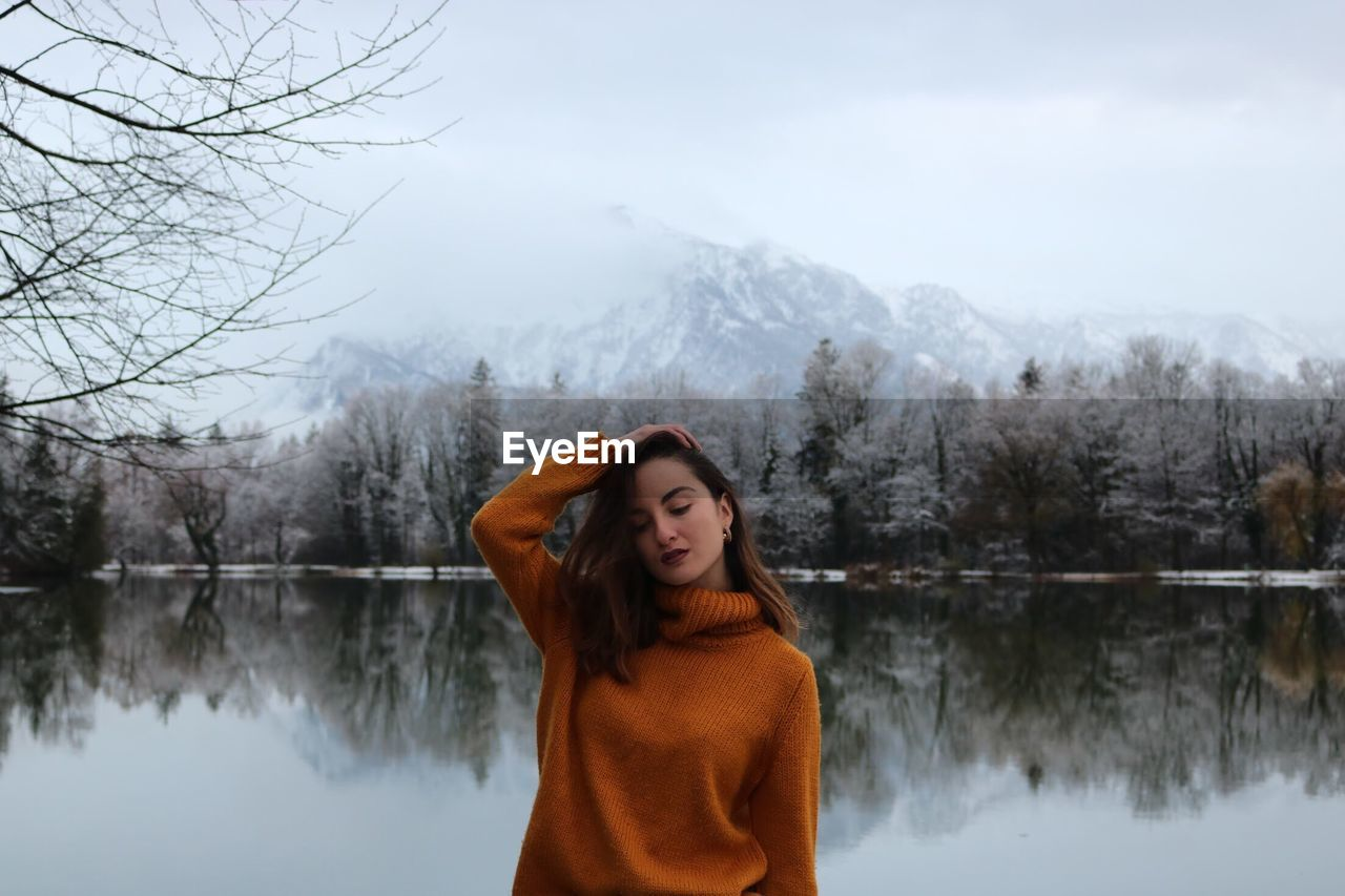 Woman with hand in hair standing by lake during winter