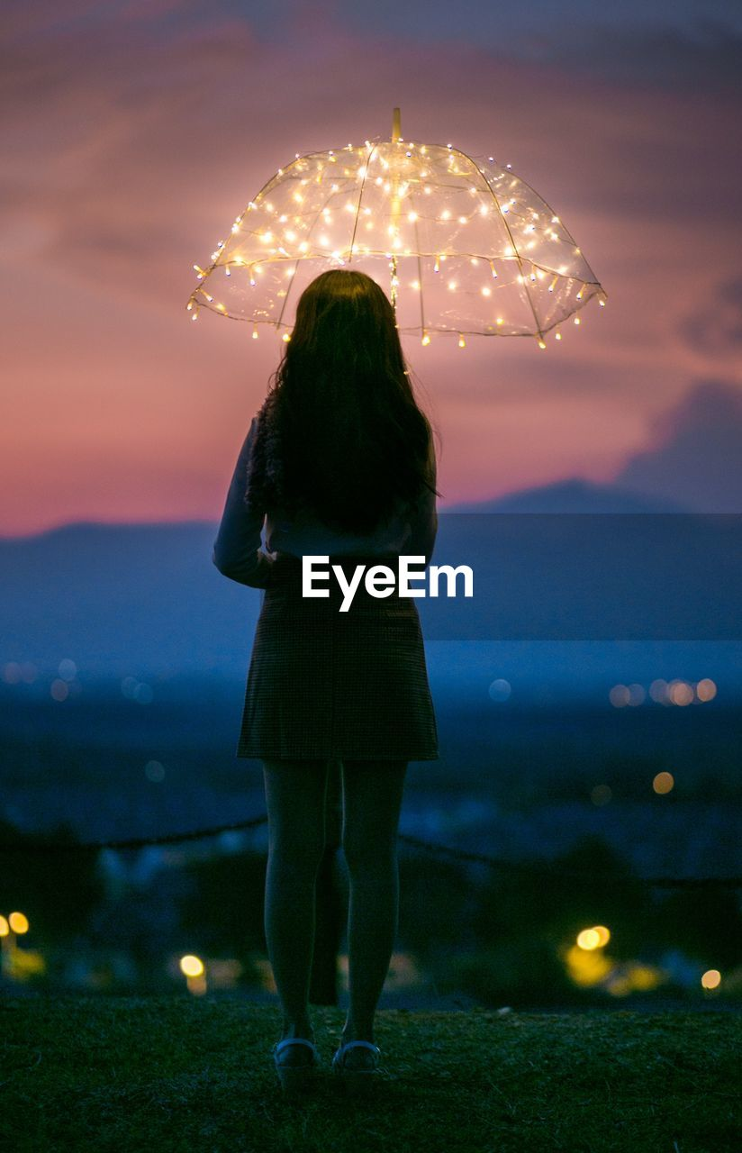 one person, real people, illuminated, rear view, full length, standing, sky, women, leisure activity, lifestyles, nature, night, adult, glowing, land, cloud - sky, firework, focus on foreground, casual clothing, outdoors, hairstyle, firework - man made object, firework display