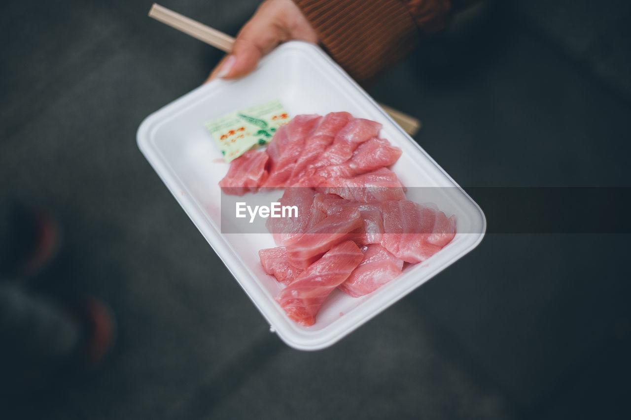 Close-Up High Angle View Of Hand Holding Sashimi