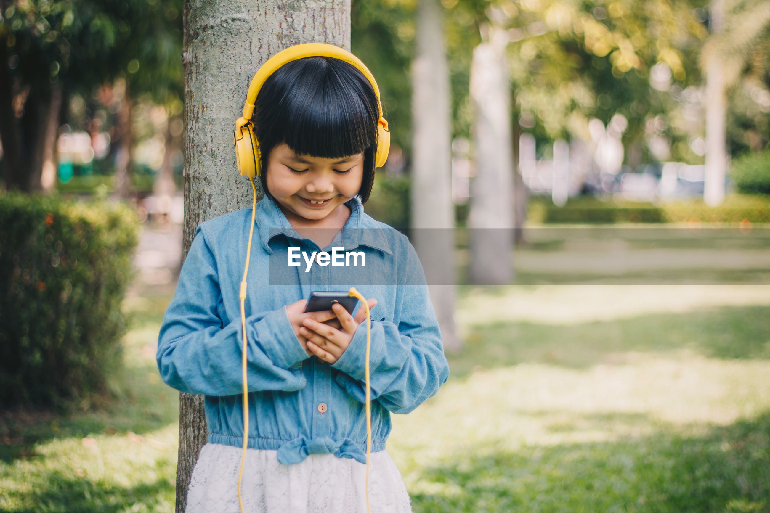 Smiling girl listening music on mobile phone while standing against tree trunk