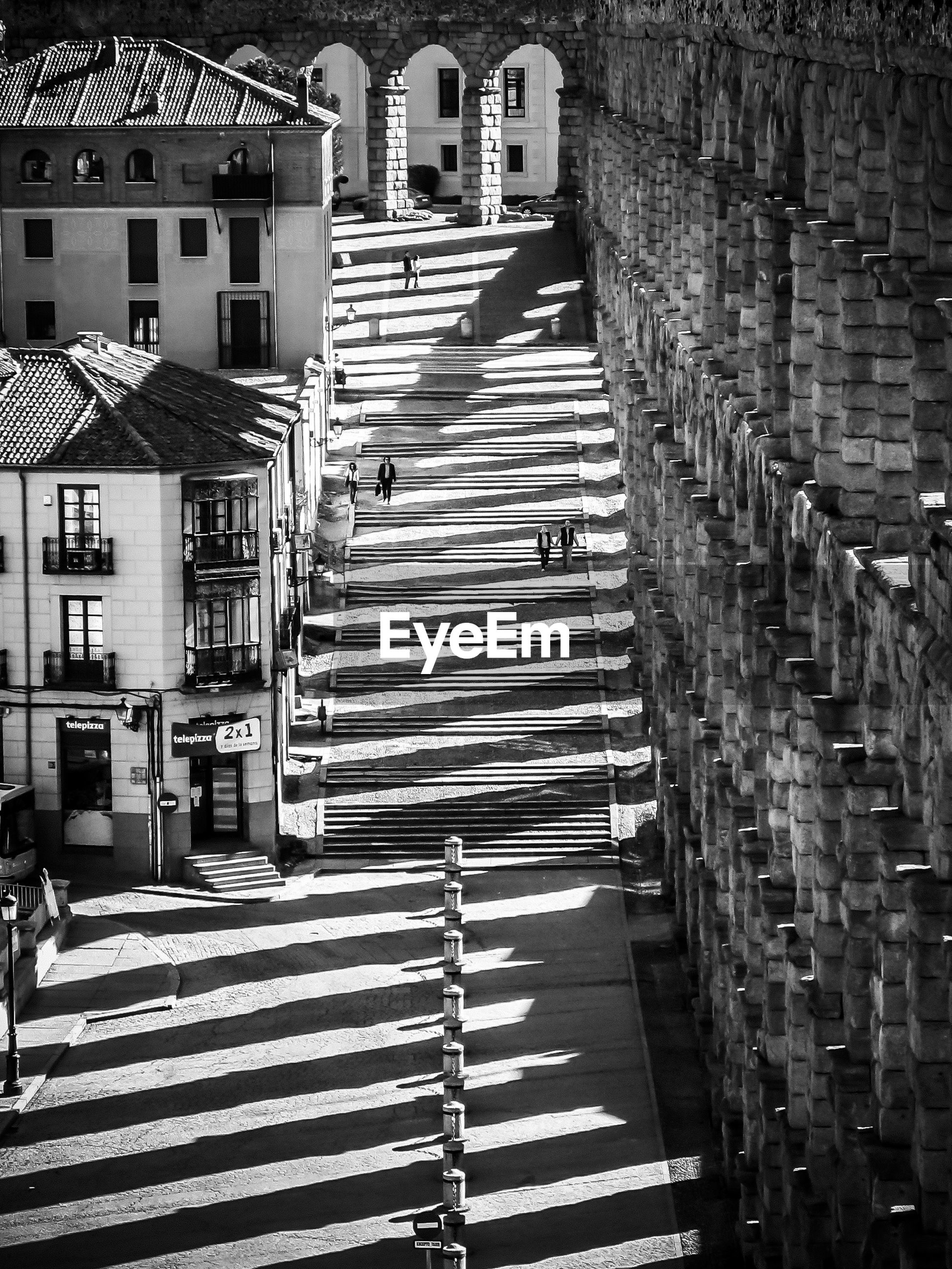 HIGH ANGLE VIEW OF STAIRCASE BY STREET AMIDST BUILDINGS IN CITY