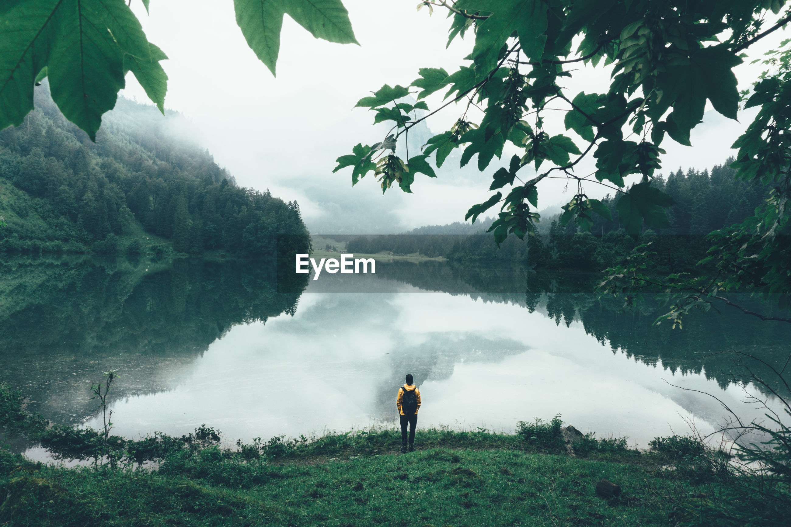 High angle view of man with backpack standing by lake during foggy weather
