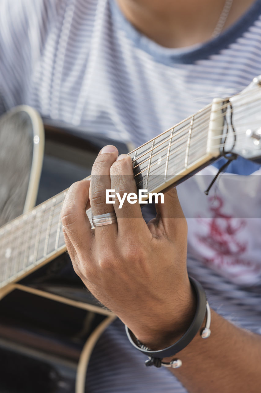 musical instrument, guitar, music, string instrument, musical equipment, one person, playing, musician, real people, arts culture and entertainment, musical instrument string, men, fretboard, string, artist, skill, human hand, plucking an instrument, midsection, holding, hand, acoustic guitar, finger, electric guitar