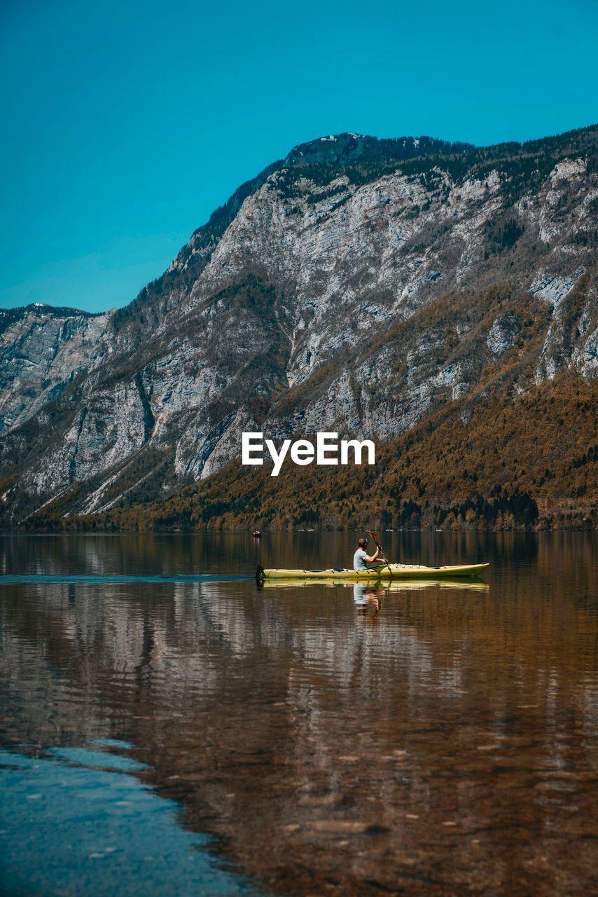 Man Kayaking On Lake Against Mountain