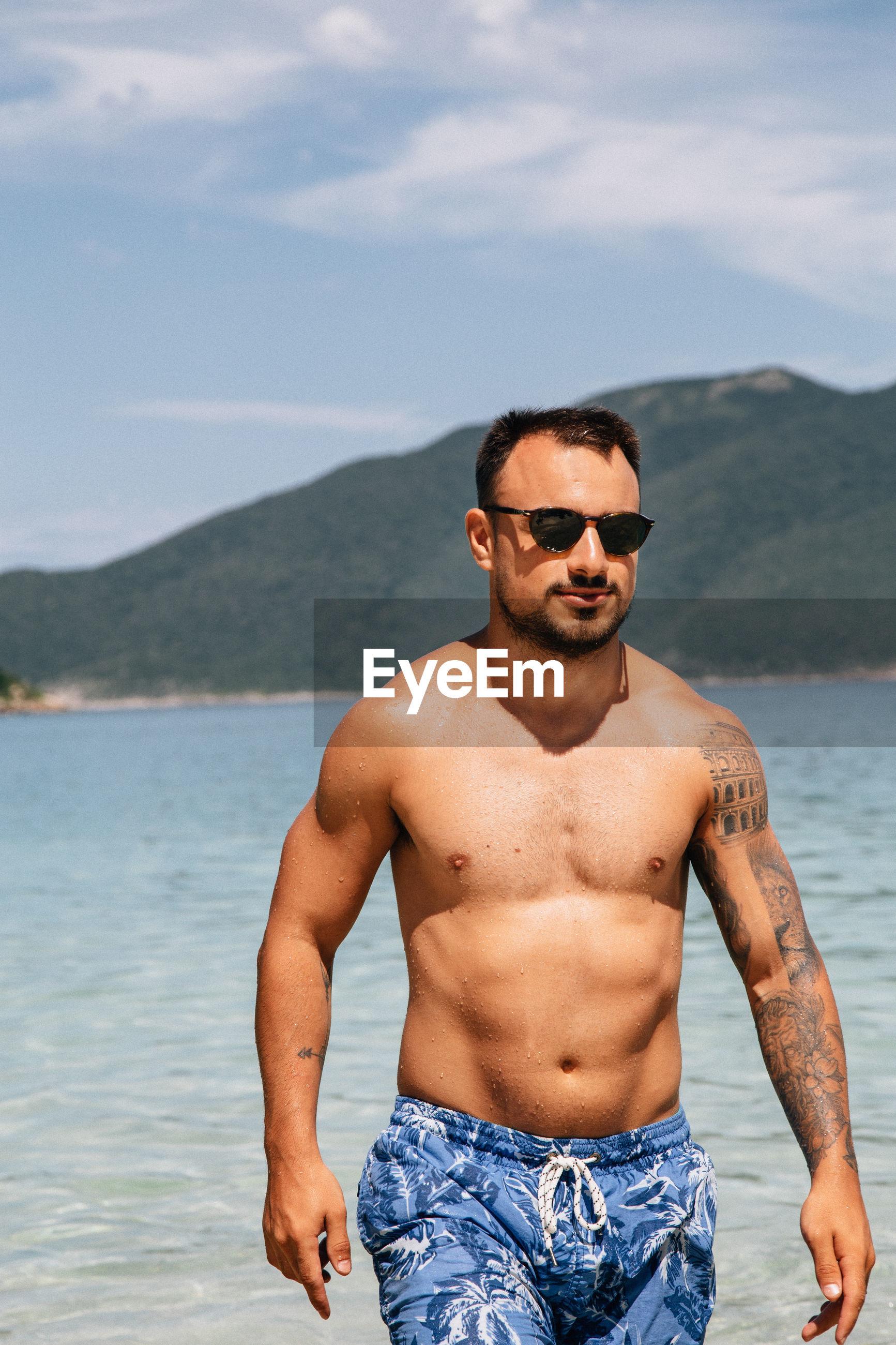 Shirtless young man walking on beach
