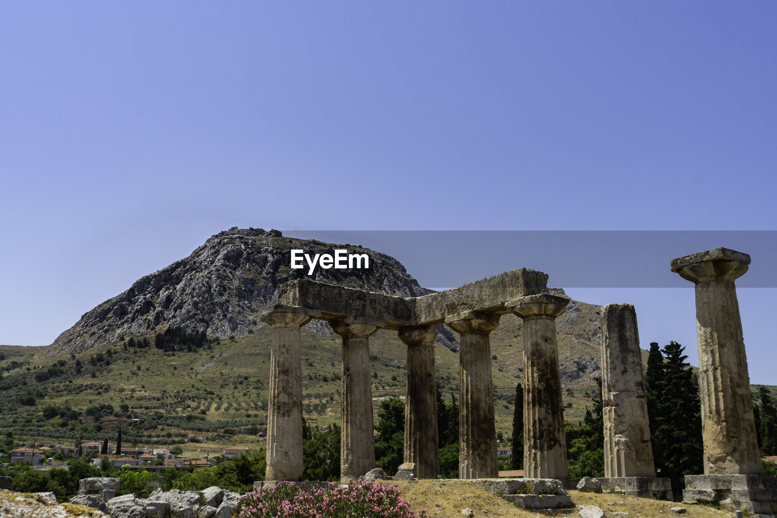 Close-up of ancient apollo temple in corinth in front of acrocorinth against blue sky