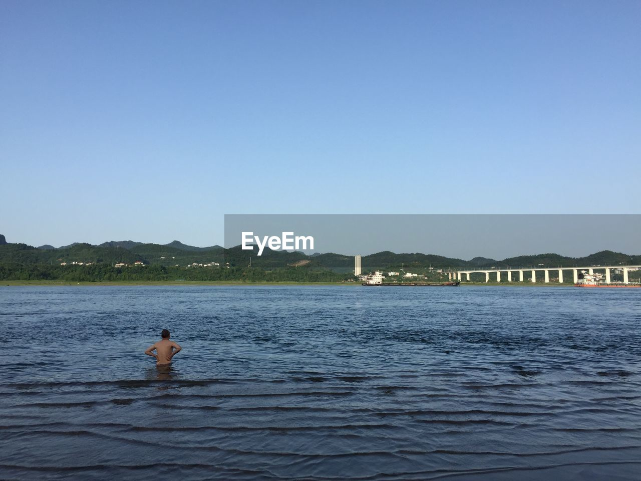 water, clear sky, copy space, leisure activity, one person, outdoors, shirtless, day, mountain, waterfront, blue, swimming, nature, swimming pool, sea, real people, sky, men, architecture, young adult, beauty in nature, one man only, people