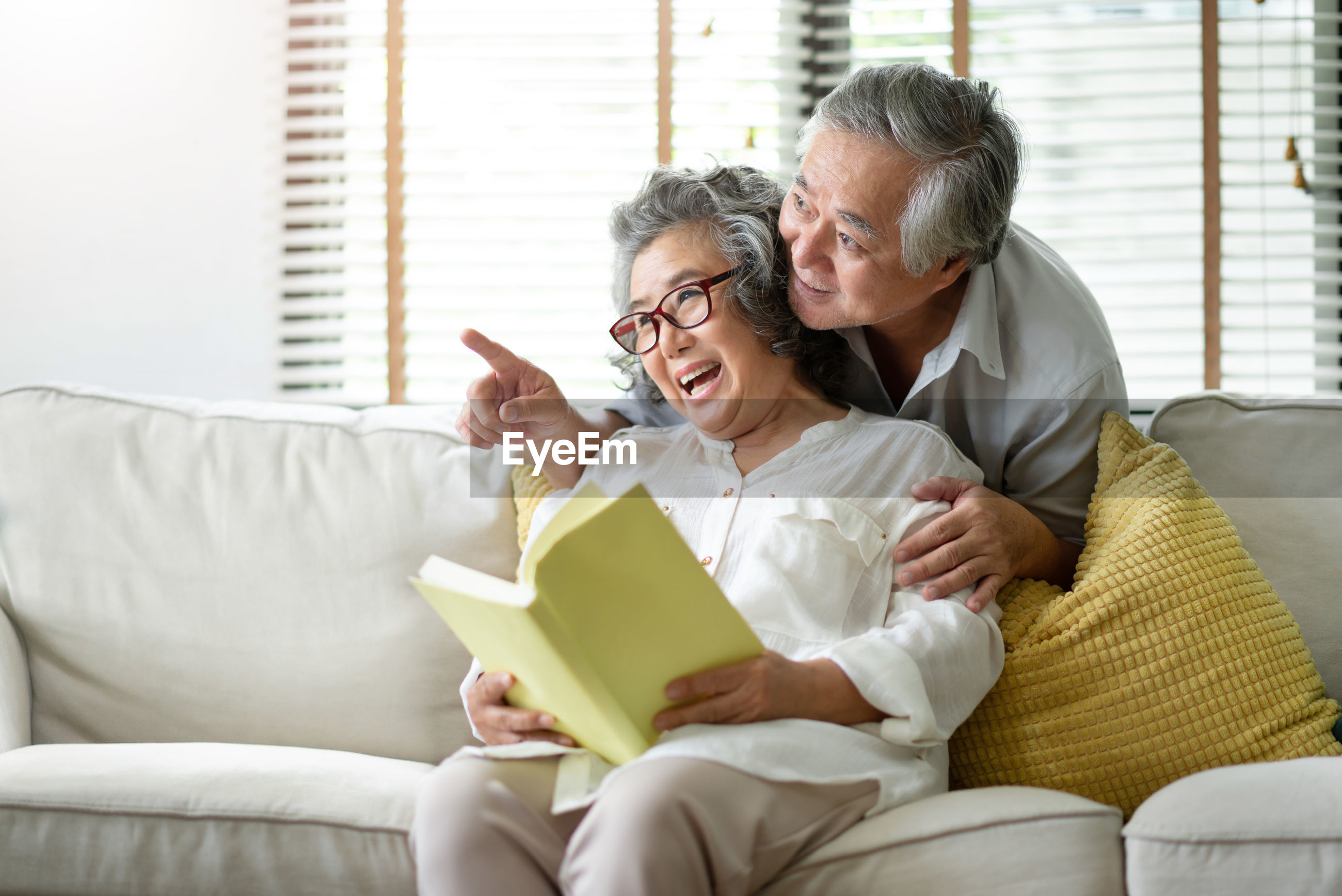 Happy senior couple laughing at home sitting on sofa