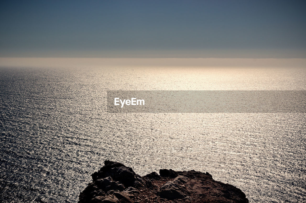 sky, scenics - nature, beauty in nature, tranquility, water, rock, tranquil scene, sea, horizon, nature, horizon over water, solid, no people, rock - object, idyllic, sunset, non-urban scene, outdoors, land