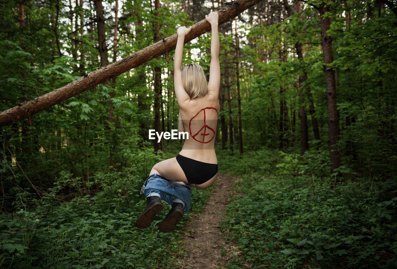 Rear View Of Shirtless Young Woman Hanging On Log In Forest