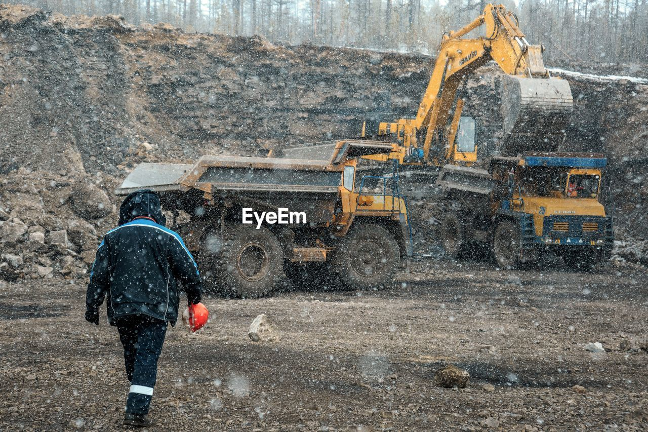 transportation, construction industry, industry, earth mover, construction site, construction machinery, machinery, day, bulldozer, road, working, one person, digging, mining, nature, mode of transportation, quarry, motion, construction vehicle, outdoors, snowing, industrial equipment