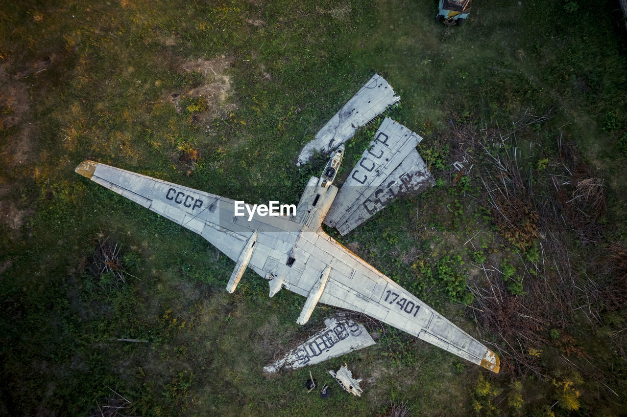 HIGH ANGLE VIEW OF AIRPLANE FLYING ABOVE ABANDONED AIRPORT