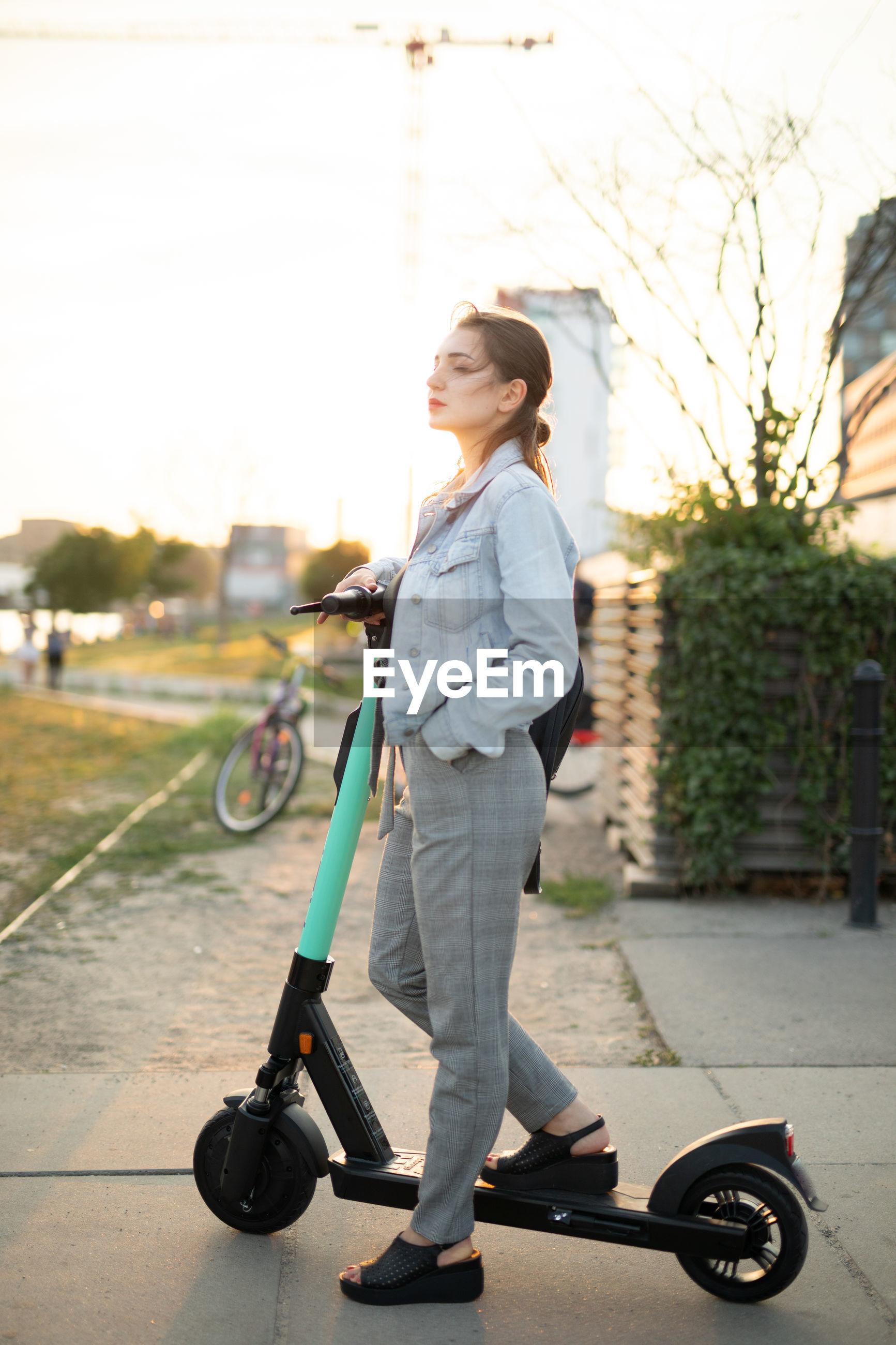 Young woman standing on push scooter against sky