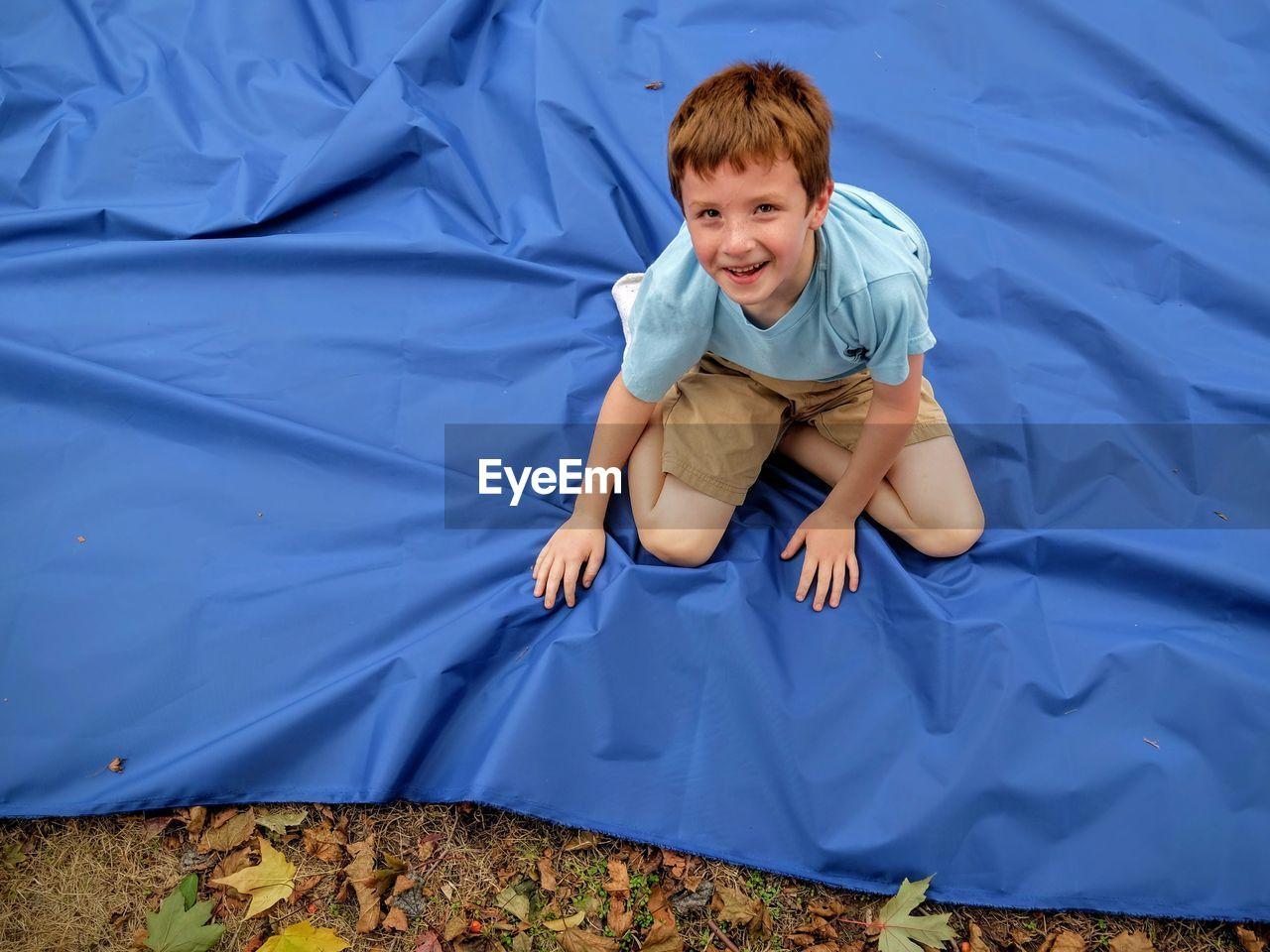 Portrait Of Boy Sitting On Blue Sheet