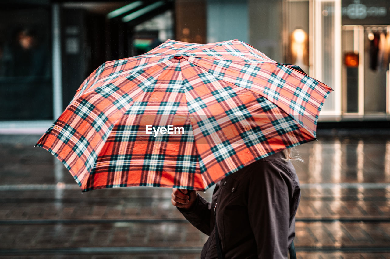 Midsection of woman holding umbrella on street in rainy season