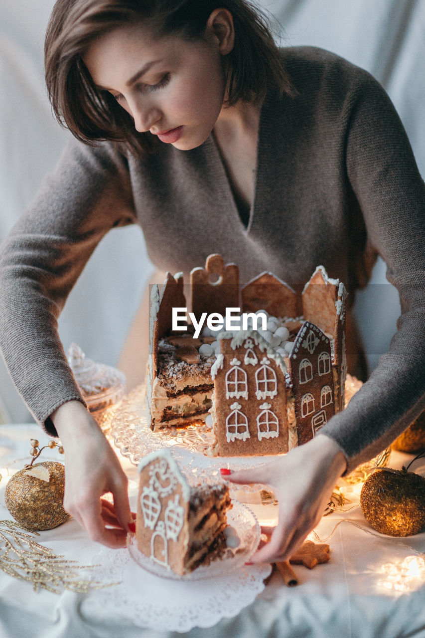Beautiful young woman arranging gingerbread house on table