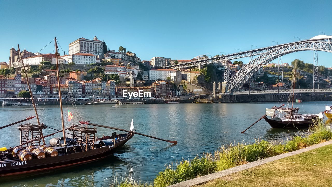 architecture, built structure, building exterior, transportation, water, nautical vessel, clear sky, river, city, outdoors, day, travel destinations, mode of transport, bridge - man made structure, town, no people, tree, nature, cityscape, sky