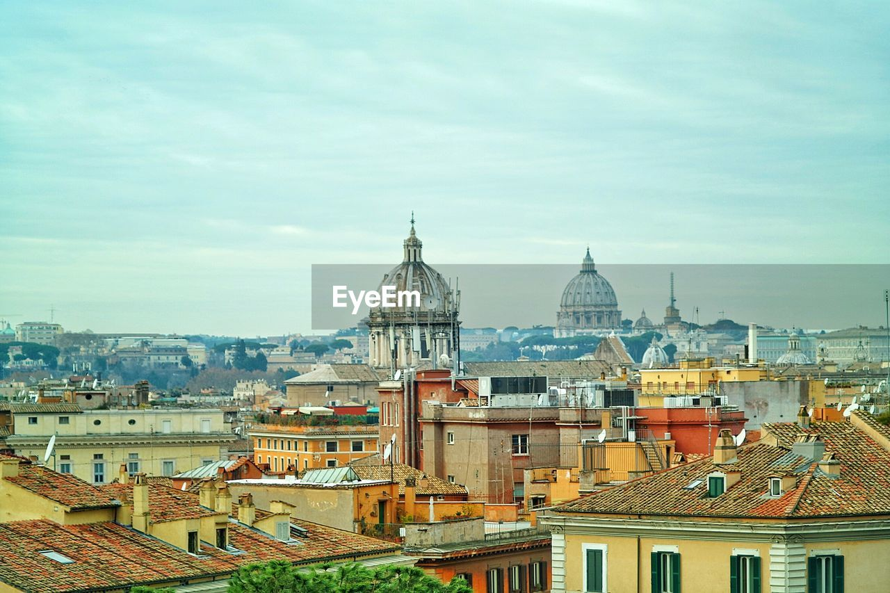 St peters basilica amidst buildings in city against sky