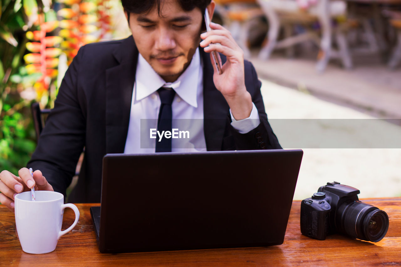 Businessman talking on smart phone while holding coffee cup by laptop and camera on table