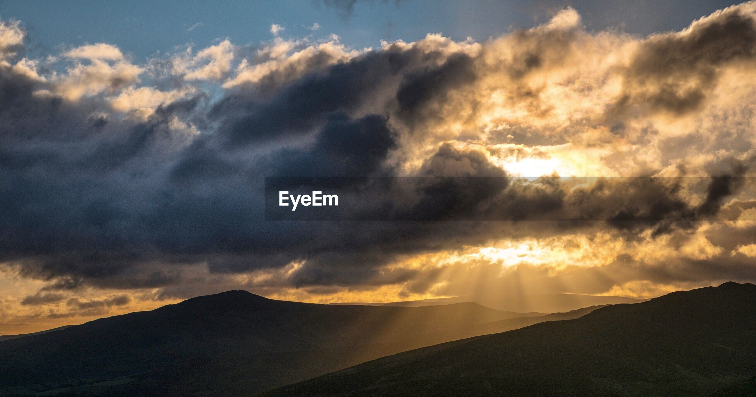 DRAMATIC SKY OVER MOUNTAINS DURING SUNSET
