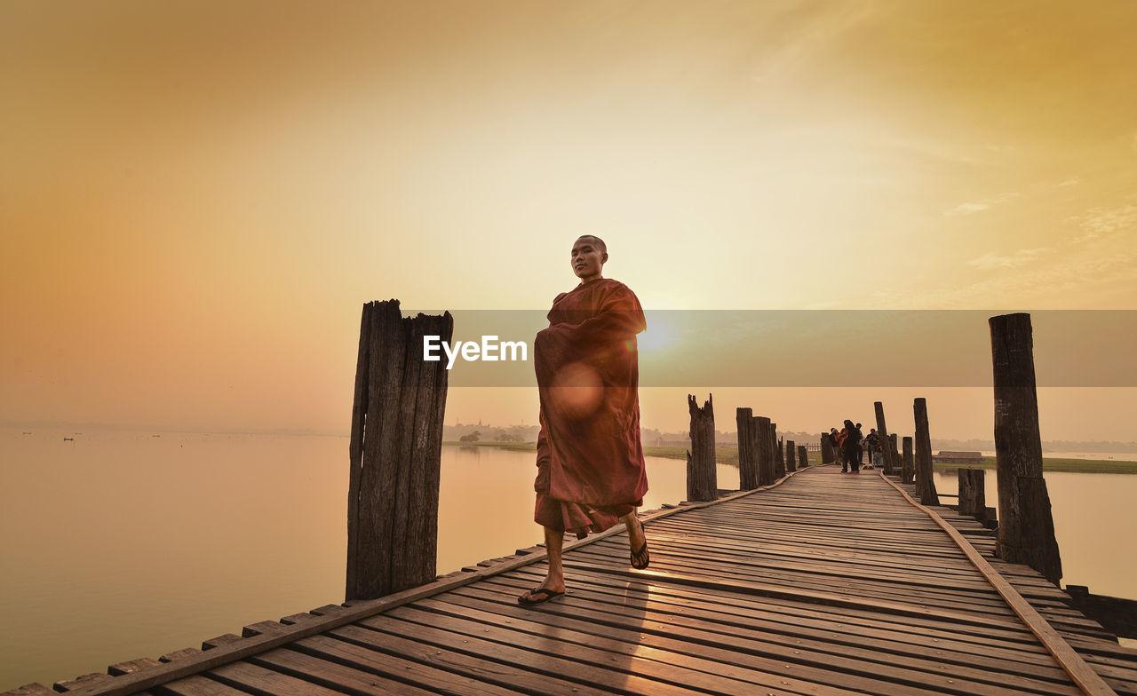 Full Length Of Monk Walking On Pier Over Sea Against Sky During Sunset