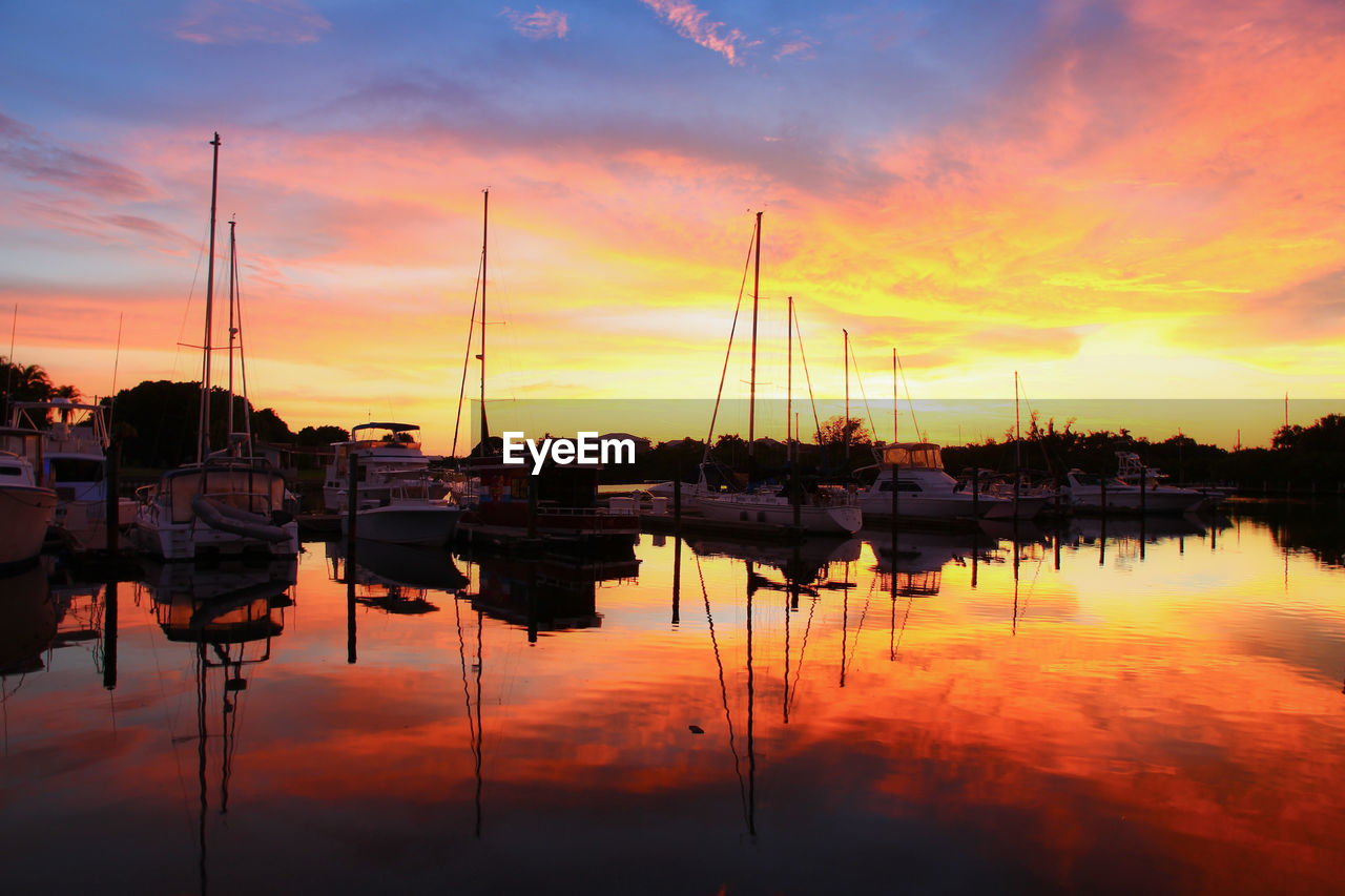 reflection, sunset, water, sky, nautical vessel, orange color, moored, tranquil scene, cloud - sky, nature, lake, standing water, tranquility, no people, outdoors, transportation, beauty in nature, mast, silhouette, scenics, waterfront, built structure, harbor, building exterior, architecture, day
