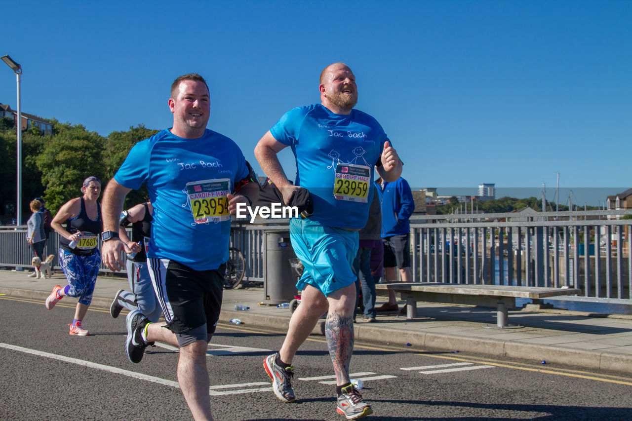 real people, front view, leisure activity, day, outdoors, sunlight, full length, lifestyles, clear sky, mid adult men, blue, young adult, sport, togetherness, sky, sports clothing, sports race, sportsman
