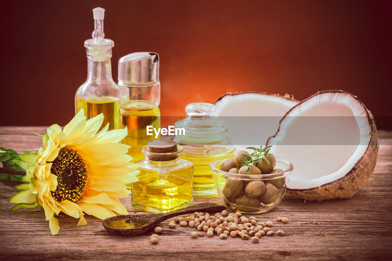 container, table, wood - material, food, freshness, food and drink, flower, wellbeing, flowering plant, indoors, bottle, plant, still life, nature, close-up, no people, spice, ingredient, bowl, oil, herb, aromatherapy