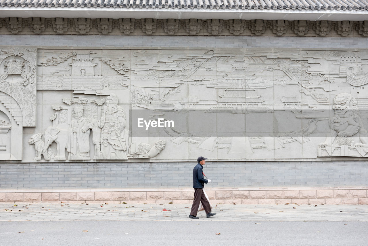 Side View Of Man Walking Against Carvings On Wall