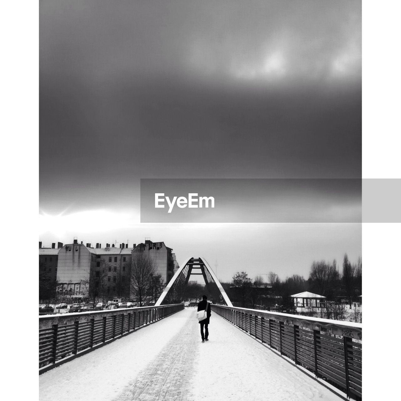 Rear View Of Person Walking On Snow Covered Bridge Against Cloudy Sky